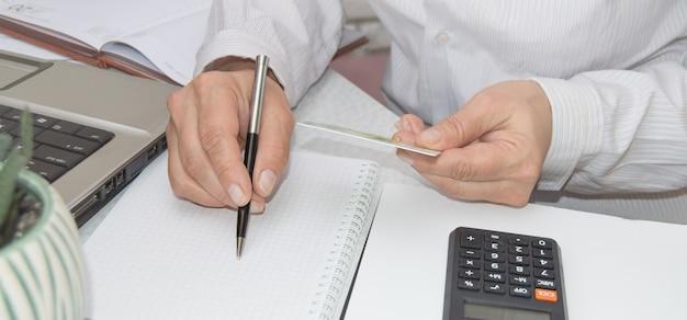 職場での支払い、税金、支払いにクレジットカードを使用する女性の手。