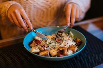 女性の手はフォークとナイフを使用して、ボウルに入れたカエサルのサラダを提供します。