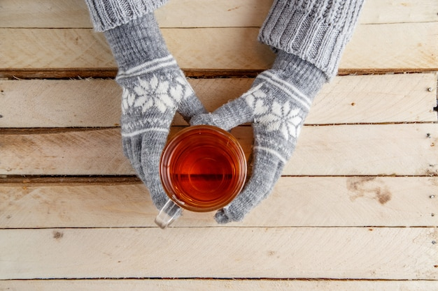 Women's hands in warm gloves holding a glass of tea