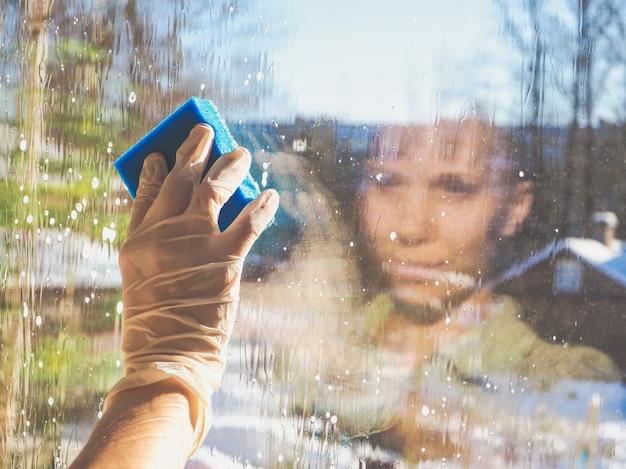 Женские руки моют окно губкой