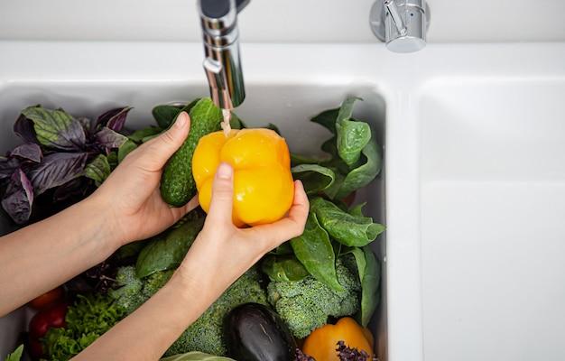 여성의 손은 현대 부엌의 부엌 싱크대에서 야채를 씻습니다. 건강 식품 개념.