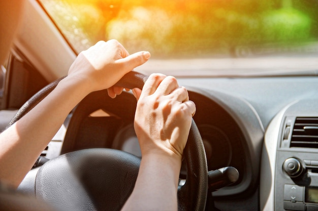 Women's hands on the wheel. close up