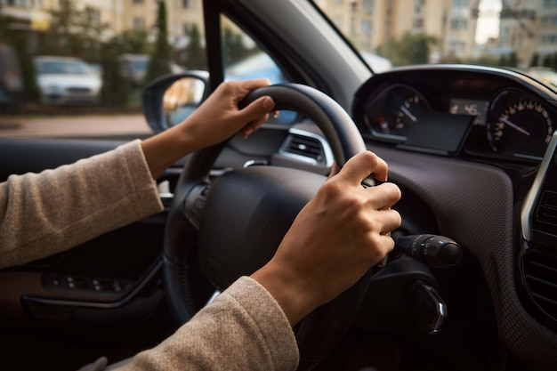 Women's hands on the wheel.