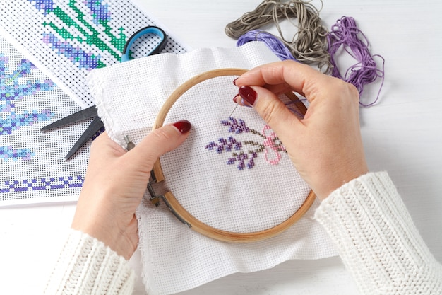 Женские руки с вышитым крестиком на ткани узорами из цветов