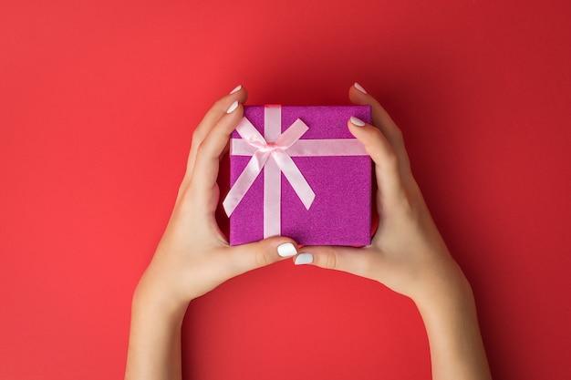 빨간색 바탕에 활과 선물 상자를 가진 여자의 손.