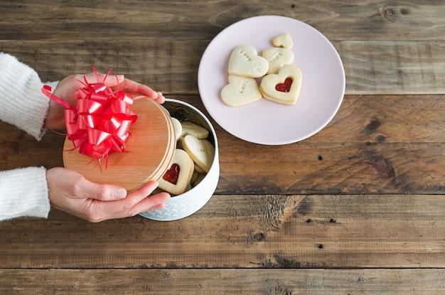 Женские руки с коробкой для печенья в форме сердца на деревянной основе и тарелкой с печеньем.