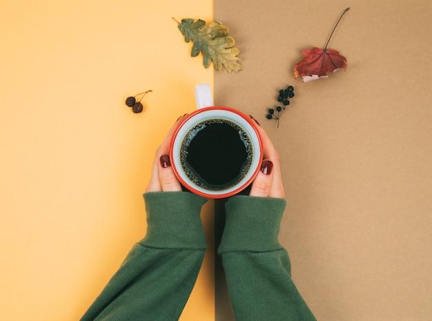2色の背景にコーヒーと乾燥した葉を持つ女性の手。秋のコンセプトです。
