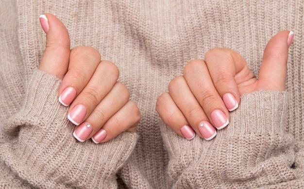 セーターの背景に長方形の爪にフレンチマニキュアとラインストーンの女性の手。冬のコンセプト