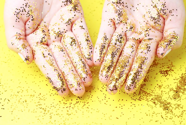 Women's hands with gold glitter close-up on a yellow surface