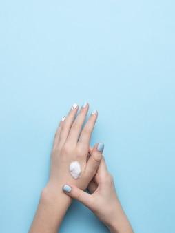 Женские руки с макияжем и каплей крема для рук