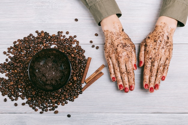 Women's hands with red nail polish in a coffee scrub