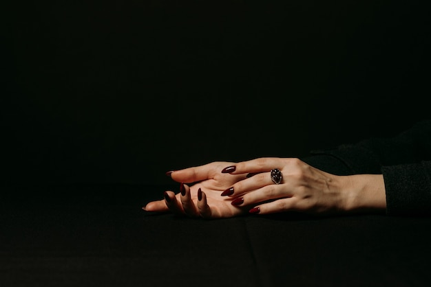 Women's hands with silver ring with garnet gem on finger with a manicure