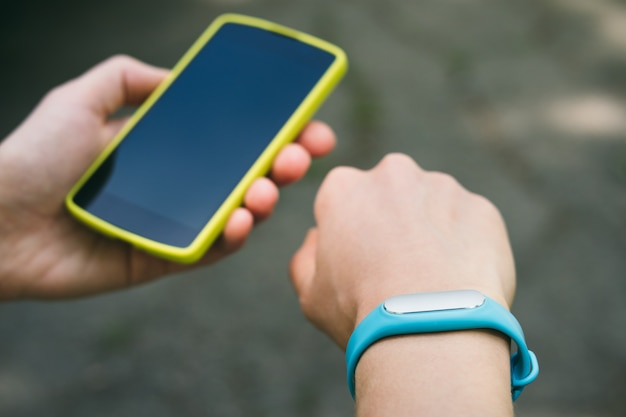 Women's hands with a sports bracelet and smart phone close-up