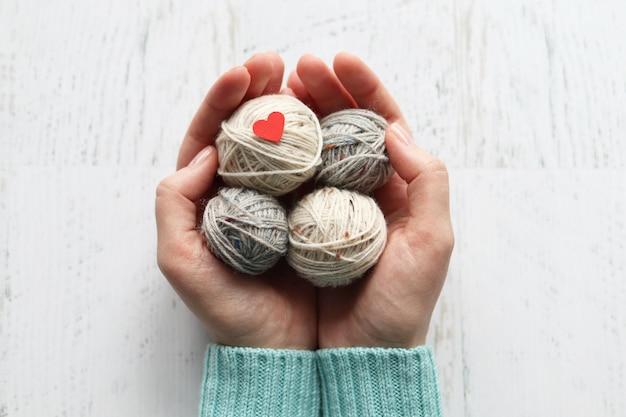 白い表面に編み糸のもつれを持つ女性の手