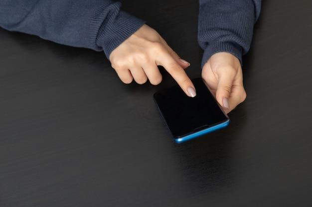 블랙 테이블 모형에서 전화를 든 여성의 손