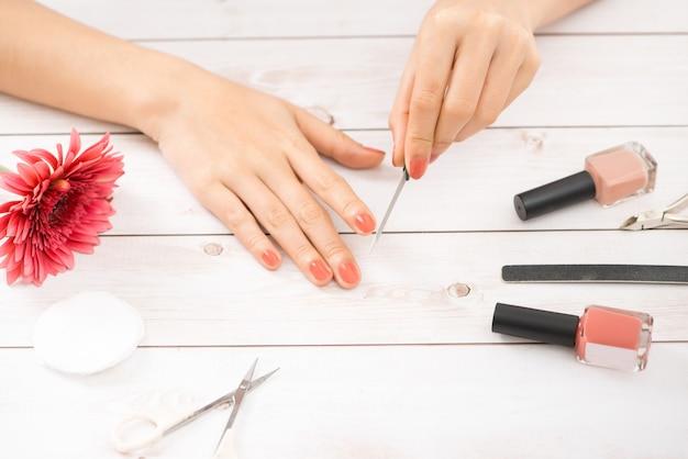 매니큐어용 도구가 있는 여성의 손. 손톱 손질.