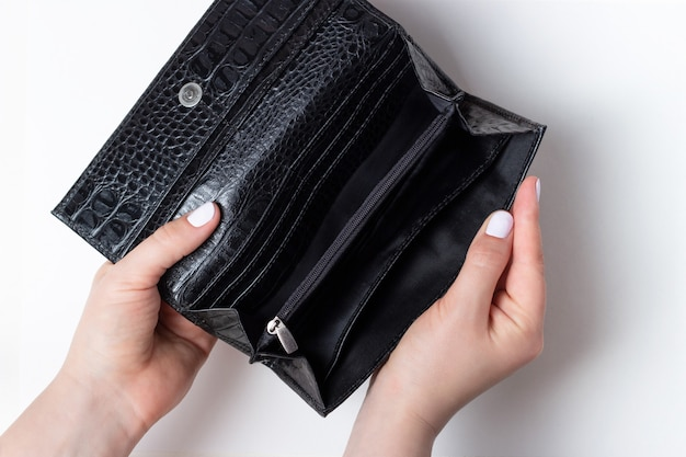 Women's hands with white manicure hold open wallet on a white table