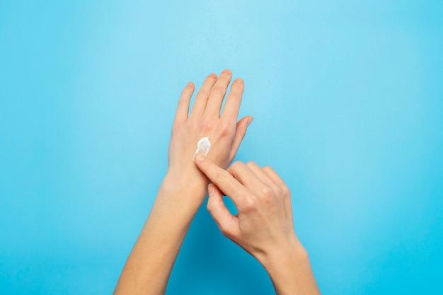 女性の手。女性は青に彼女の手にクリームを塗ります。化粧品、スキンケア、ローション、化粧、スパの概念。