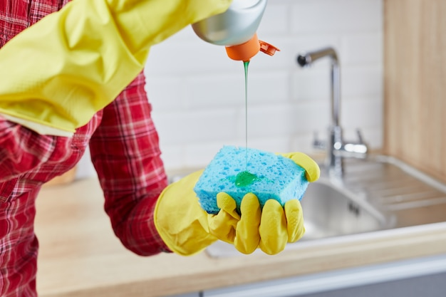 Women's hands in yellow protective glove with bottle of detergent gel and sponge