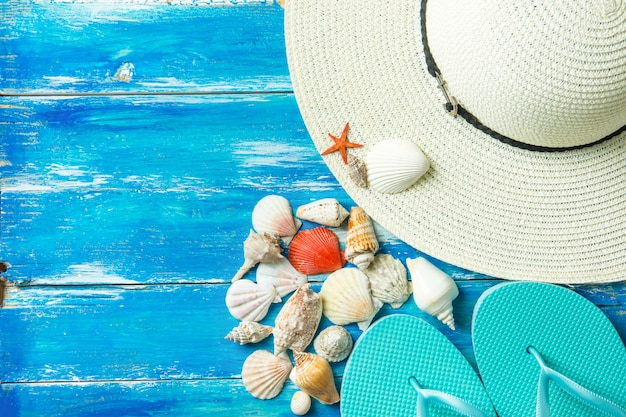 Women's hat slippers various kinds of spiral flat sea shells red star fish on aged plank wood blue background.
