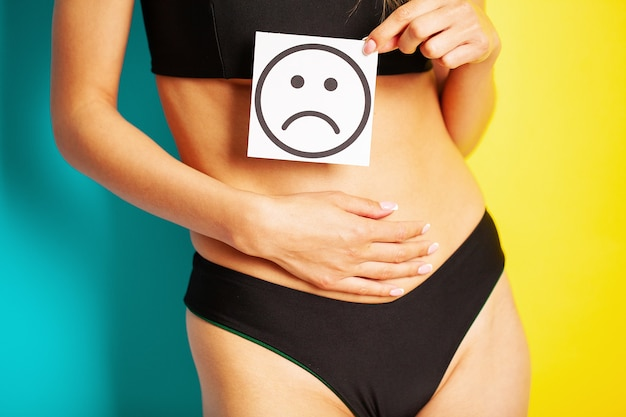 Women's health, women's body holds a card of a sad smile near the belly.