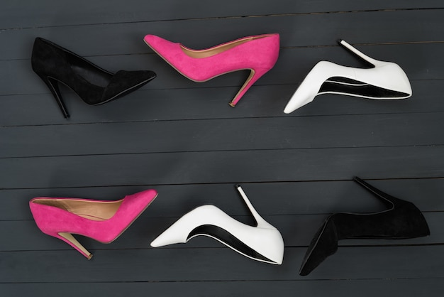 Women's high heel shoes in different colors. black wood background. fashion concept
