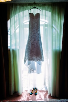 Women's high-heeled shoes and long white dress of the bride in hotel room.