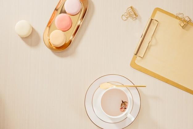 Рабочее пространство домашнего офиса женщин с буфером обмена, миндальным печеньем, ручкой, кружкой кофе на пастельном фоне. плоская планировка, концепция образа жизни вид сверху.