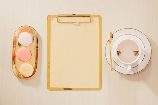 클립 보드, 마카롱, 펜, 파스텔 배경에 커피 잔이있는 여성의 홈 오피스 작업 공간. 평면 위치, 최고보기 라이프 스타일 개념.