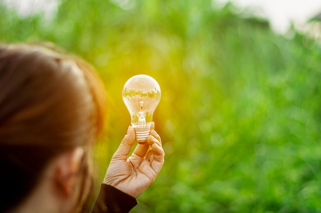 Women's is holding sparking light bulb against nature on green leaf. - new idea and innovation concept.