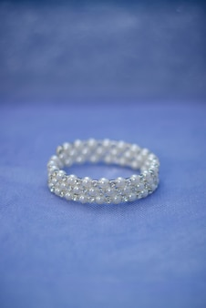 Women's jewelry bracelet in white pearls beads for bride close up on blue background