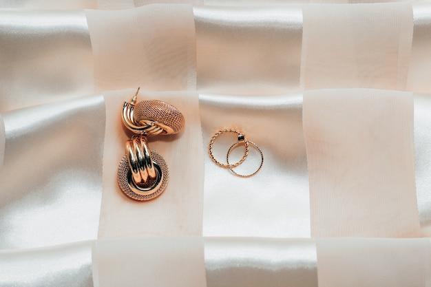 Женские украшения, серьги, модные украшения, кольца на шелковом фоне.
