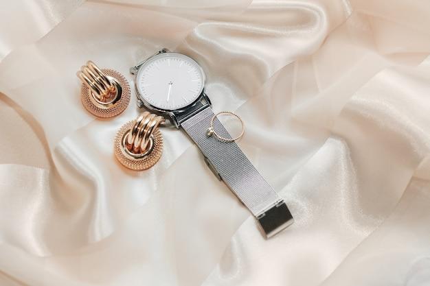 여성용 보석 귀걸이, 최신 유행의 보석, 시계, 실크 배경의 반지.