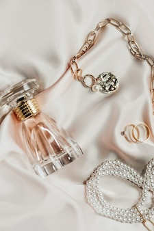 Женские украшения, золотая цепочка, модные украшения, духи на шелковом фоне.