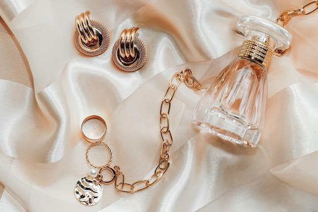 Женские украшения, золотая цепочка, модные украшения, духи на шелковой поверхности.