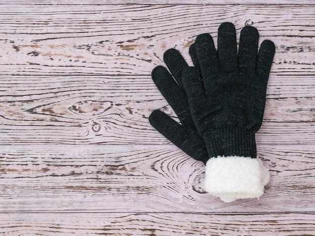木製の背景に女性のニット手袋。ファッションの女性の冬のアクセサリー。フラットレイ。