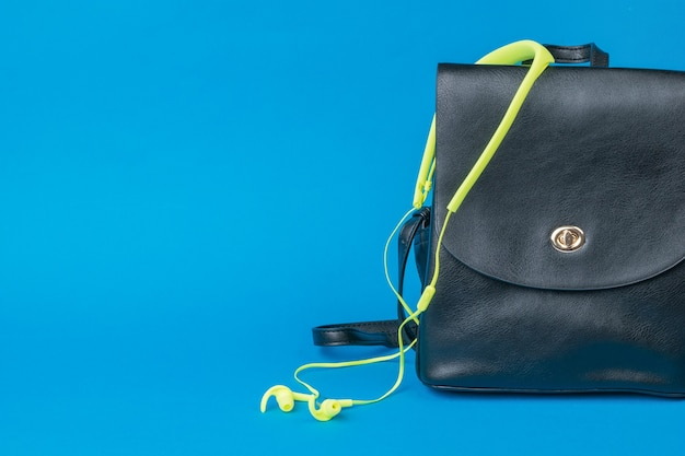 Women's leather backpack and yellow headphones on a blue background. the concept of tourism and education.