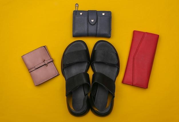 Женские кожаные сандалии и кошельки на желтом фоне. женские аксессуары. вид сверху. плоская планировка