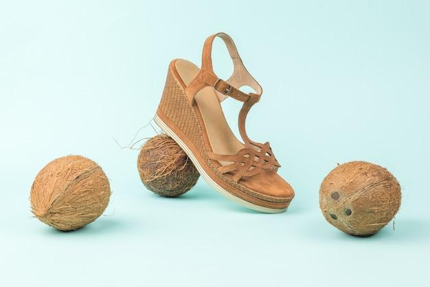 女性の革の夏のかかとの高い靴と3つのココナッツ。天然素材の靴。