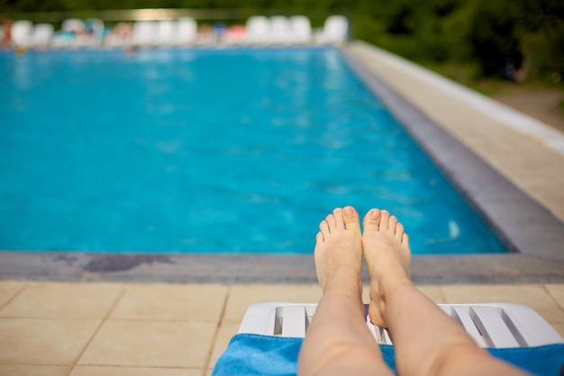 Women's legs on the background of the pool with blue water in the open air.