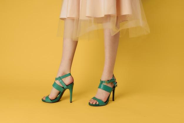 여자 다리 녹색 신발 유행 신발 노란색 벽.