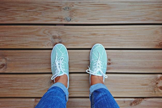 복사 공간이 있는 테라스 보드에 민트 그린 운동화를 신고 있는 여성의 다리