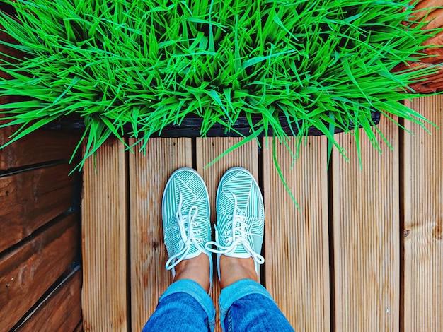 Women's legs in mint sneakers on terrace board with artificial grass in flowerpot