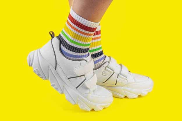 Women's legs in multi-colored socks in the form of a rainbow with white sneakers on a colored background, close-up, lgbtq, pride