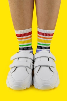 Women's legs in multi-colored socks in the white sneakers on colored background, close-up, vertical image