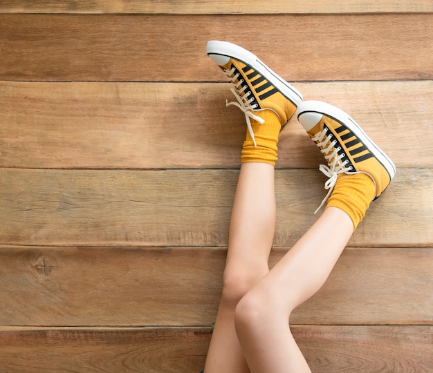 Women's legs in a mustard sneakers