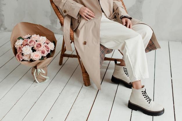 白い背景の上の女性の足。花の花束と女の子の足。女性の足元にあるバラの花束。