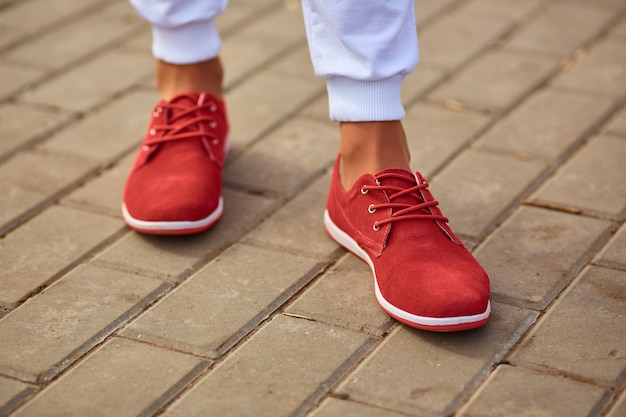 Women's legs in red sneakers and white sweatpants close up