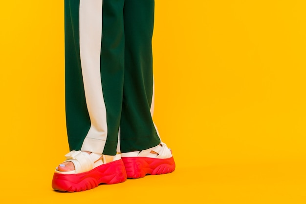 Women's legs in sport sandals with red soles and green pants with stripes on a yellow background.
