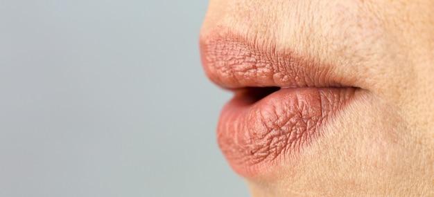 女性の唇はアヒルのようにチューブに伸ばされています。